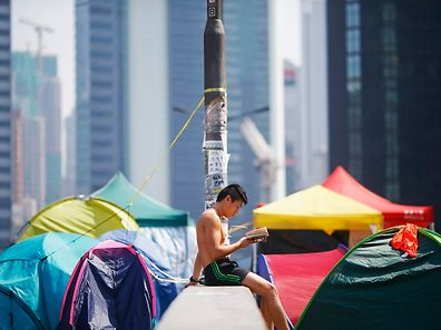 A man reads a book between tents set-up on a closed road in a part of Hong Kong's financial central district occupied by pro-democracy protesters October 27, 2014