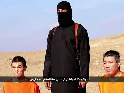 Japanese hostages Kenji Goto (L) and Haruna Yukawa (R) in orange jumpsuits with a black-clad militant brandishing a knife as he addresses the camera in English, standing between them at an undisclosed location