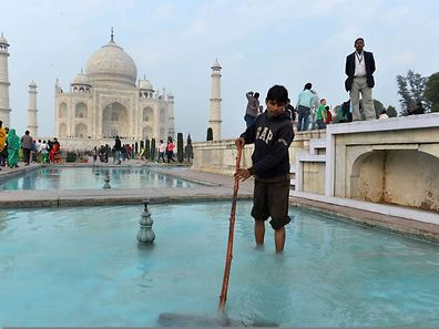 An Indian worker cleans a water pond inside the grounds of the Taj Mahal ahead of US President Barack Obama's visit in Agra.