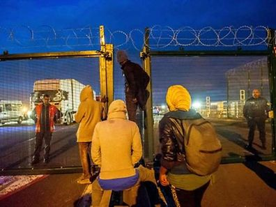 TOPSHOTS French gendarmes face migrants on the Eurotunnel site near the boarding docks in Coquelles near Calais, northern France, on late July 29, 2015. One man died Wednesday in a desperate attempt to reach England via the Channel Tunnel as overwhelmed authorities fought off hundreds of migrants, prompting France to beef up its police presence. AFP PHOTO / PHILIPPE HUGUEN