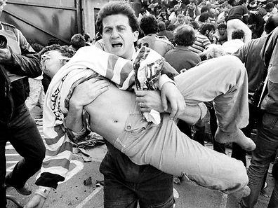 Ein Fußballfan trägt einen Verletzten aus dem Heysel-Stadion.