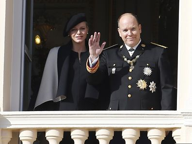 Prince Albert II of Monaco waves next to Princess Charlene of Monaco from the balcony of the Monaco Palace during celebrations marking Monaco's National Day in Monacoon November 19