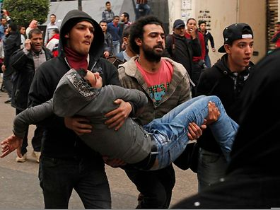 Anti-government protesters help an injured protester when pro-government protesters threw stones during a protest in front of the press syndicate in Cairo January 25, 2015. Three people were killed during pro-democracy protests in Egypt and a bomb wounded two policemen on Sunday, the anniversary of the 2011 uprising that toppled autocrat Hosni Mubarak, security sources said.