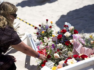 A woman lays flowers at the site of a shooting attack on the beach in front of the Riu Imperial Marhaba Hotel in Port el Kantaoui, on the outskirts of Sousse
