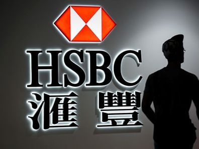 A man walks past a logo of the HSBC bank in Hong Kong on August 3, 2015.