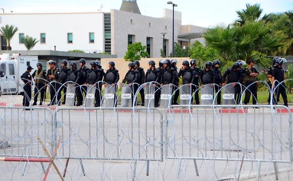 Riot police protect the US embassy in Tunisia
