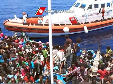 Migrants sit in a boat during a rescue operation on July 23, 2015 off the coast of Libya, as part of the Frontex-coordinated Operation Triton