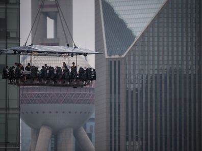 """Diners are suspended from a crane as they enjoy a meal organized by the """"Dinner in the Sky"""" over Lujiazui Financial District in Shanghai on June 27, 2014. Dinner in the Sky kicked off in Shanghai on June 27 with 22 diners enjoying their meal in a sky box suspended from a crane about 50 meters above the ground, at a price that varies from 1,888 yuan (302 USD) to 8,888 yuan (1,423 USD) . AFP PHOTO CHINA OUT"""
