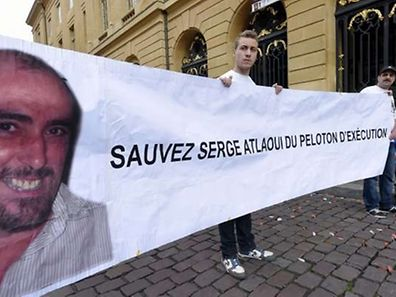 """Protesters hold a banner with the portrait of Serge Atlaoui and reading """"Save Serge Atlaoui from the firing squad"""" on April 25, 2015 in Metz, eastern France, in support of French national Serge Atlaoui, on death row in Indonesia for drug trafficking. An official said on April 25 Atlaoui will not be included in an upcoming batch of executions, as he still has a legal appeal outstanding.   AFP PHOTO / ALEXANDRE MARCHI"""