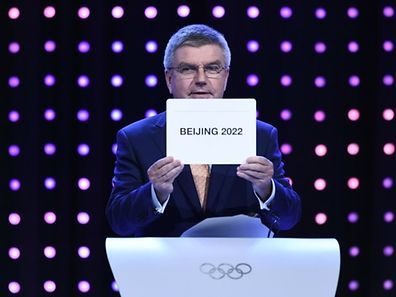 Thomas Bach holds a card showing that Beijing has been chosen to host the 2022 Olympic Games