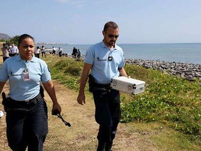 Des policiers emportent des débris métalliques sous scellés.