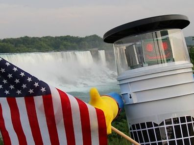 hitchBOT poses with the US flag at Niagra Falls