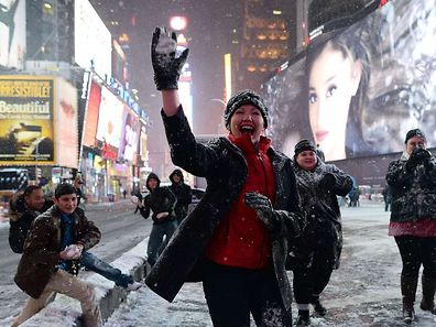 A group of youth from Texas play snow-ball-fighting on a deserted street in New York's Times Square during a snow storm on January 26, 2015.