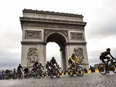 Great Britain's Christopher Froome, wearing the overall leader's yellow jersey, (2nd R) rides with the pack  past the Arc de Triomphe in Paris  during the 109,5 km twenty-first and last stage of the 102nd edition of the Tour de France cycling race on July 26, 2015, between Sevres and Paris. AFP PHOTO / ERIC FEFERBERG