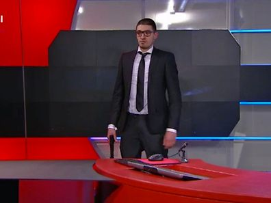 A man wielding a pistol stands in a TV studio of Dutch national broadcaster NOS