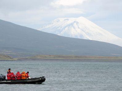 Touristen fahren bei Schumschu in Schlauchbooten zurück zum Kreuzfahrtschiff. Im Hintergrund ist der Vulkan Alaid zu sehen.