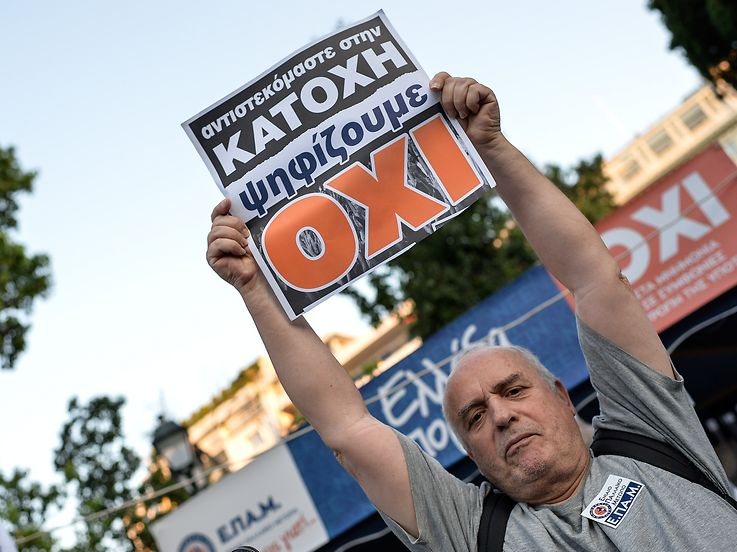 "A man holds a board which reads ""No"" for the vote in the Greek referendum, as he celebrates at Syntagma Square in Athens on July 5, 2015 after the first exit-polls of a referendum on usterity measures. Greek voters headed to the polls today to vote in a historic, tightly-fought referendum on whether to accept worsening austerity measures in exchange for more bailout funds, in a gamble that could see the country crash out of the euro. AFP PHOTO / ANDREAS SOLARO"