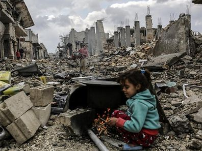 Kurdish Syrian girls are pictured among destroyed buildings in the Syrian Kurdish town of Kobane