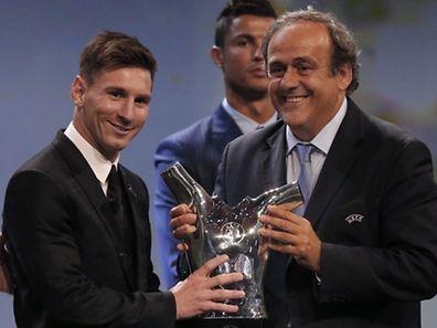Lionel Messi nimmt die Trophäe von UEFA-Präsident Michel Platini entgegen.