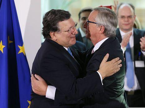 Le président sortant de la Commission, José Manuel Barroso, félicite son successeur lors d'une cérémonie au Berlaymont à Bruxelles, le 30 octobre 2014