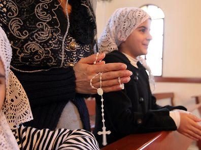 Une femme et ses enfants chrétiens assyriens, qui ont fui le conflit en Syrie, prient pour les 220 chrétiens assyriens enlevés par le groupe Etat islamique.