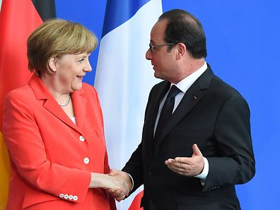 Angela Merkel (l.) and François Hollande shake hands in Berlin
