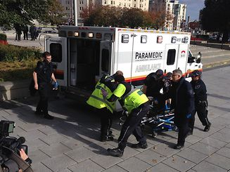 Police and paramedics transport a wounded Canadian soldier on October 22, 2014 in Ottawa, Ontario. Canadian police backed by armored vehicles surrounded parliament in Ottawa on Wednesday after a soldier was shot while guarding a nearby monument. Witnesses said they saw a gunman running to the parliament building after the shooting. Heavily armed police raced to seal off the building and the office of Canadian Prime Minister Stephen Harper. AFP PHOTO/MICHEL COMTE