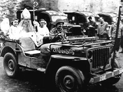 A photo from December 1944 shows Richard Brookins dressed as St Nick being driven in a Jeep around Wiltz