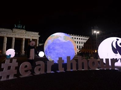 "A WWF activist dressed as a panda bear stands next to an illuminated globe in front of the Brandenburger Gate in Berlin during the the global climate change awareness campaign ""Earth Hour"" on March 28, 2015. Millions are expected to take part around the world in the annual event organised by environment conservation group WWF, with hundreds of well-known sights including the Eiffel Tower in Paris and the Seattle Space Needle set to plunge into darkness for an hour to highlight the plight of the planet.  AFP PHOTO / JOHN MACDOUGALL"