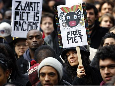"Demonstrators hold signs reading ""Black Pete is Rascism"" and ""Free Black Pete"" during a demonstration against Zwarte Piet in Amsterdam last year"