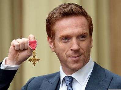 British actor Damian Lewis holds his Officer of the Order of the British Empire (OBE) medal after an investiture ceremony at Buckingham Palace in London on November 26, 2014.
