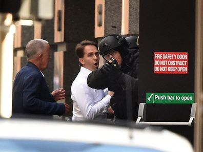 Two hostages (L) run for cover behind a policeman (R) during a hostage siege in the central business district of Sydney on December 15, 2014.