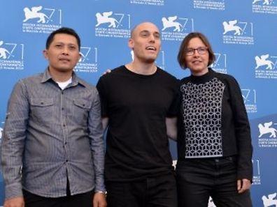 """De gauche à droite, le personnage principal du film Adi Rukun, le réalisateur américain Joshua Oppenheimer et la productrice Signe Byrge Sorensen pour la présentation du film """"The Look of Silence"""", le 28 août 2014, à la Mostra de Venise."""