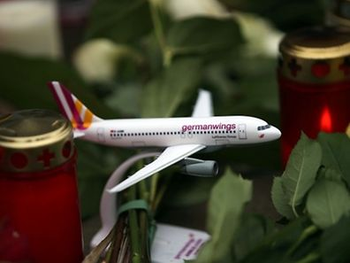 A toy airplane of German airline Germanwings is placed between candles and flowers at the airline's headquarter in Cologne, western Germany, on March 27, 2015. Germany will hold a national memorial ceremony and service for victims of a Germanwings flight that crashed in the French Alps, killing all 150 aboard, on April 17, regional authorities said. AFP PHOTO / DPA / OLIVER BERG
