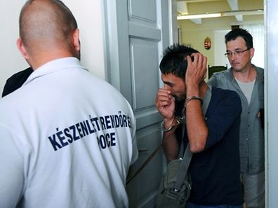 One (C) of four suspects is led by a Hungarian police officials into the Kecskemet courtroom on August 29, 2015. Four suspects in the deaths of 71 migrants found in an abandoned truck in Austria arrived Saturday for a court hearing in Hungary.  AFP PHOTO / ATTILA KISBENEDEK