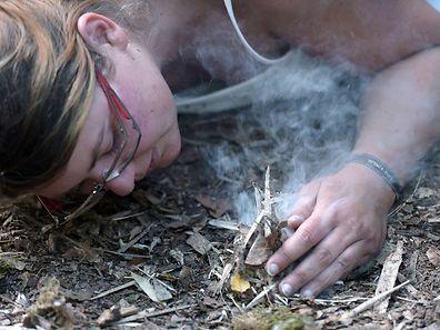 """Une femme apprend à allumer un feu lors d'un stage de """"vie sauvage"""" à Rhodes, animé par Kim Pasche, 32 ans, un archéologue suisse spécialisé en préhistoire devenu trappeur dans le Nord canadien."""