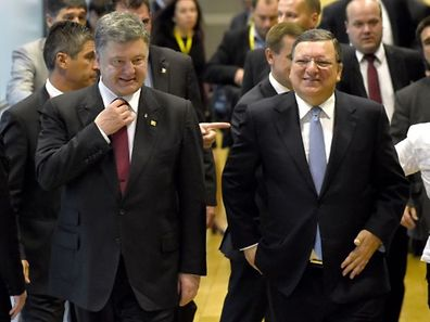 EU Commission Chairman Jose Manuel Barroso (R) welcomes Ukrainian President Petro Poroshenko on August 30, 2014 before a European Union summit at EU headquarters in Brussels. EU leaders are expected to agree on tougher sanctions against Russia after NATO charged that Moscow now had 1,000 troops fighting in support of rebel forces in southeastern Ukraine and had shipped in large amounts of heavy weaponry.  AFP PHOTO / JOHN THYS