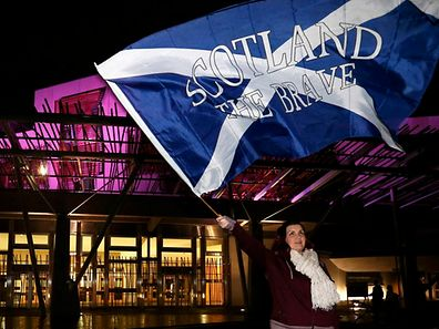 "A supporter from the ""Yes"" Campaign waves a Scottish Saltire flag outside the Scottish Parliament in Edinburgh, Scotland September 19, 2014."