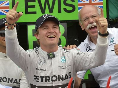 Mercedes-AMG's German driver and race winner Nico Rosberg (C), Dieter Zetsche (R), CEO of the Daimler AG, and Mercedes-AMG's British driver Lewis Hamilton (L, hidden) celebrate after the German Formula One Grand Prix at the Hockenheimring racing circuit in Hockenheim