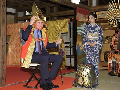Britain's Prince William (L), Duke of Cambridge, tries on a samurai costume as Japanese actress Mao Inoue in kimono looks on, during his visit a Taiga historical drama studio set at NHK (Japan Broadcasting Corporation) in Tokyo February 28, 2015