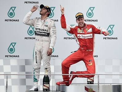 Ferrari's German driver Sebastian Vettel celebrates on the podium after winning the Formula One Malaysian Grand Prix