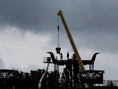 Workers set up a stage during rainfall two days prior to the start of the 26th heavy metal Wacken Open Air (WOA) Festival 2015 in Wacken, northern Germany on July 28, 2015. The heavy metal festival will take place from July 30 until August 1, 2015.  AFP PHOTO / DPA / AXEL HEIMKEN +++ GERMANY OUT