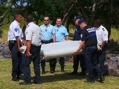 French gendarmes and police carry a large piece of plane debris which was found on the beach in Saint-Andre, on the French Indian Ocean island of La Reunion
