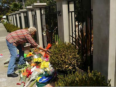 A woman places flowers outside the home of actor Robin Williams in Tiburon, California