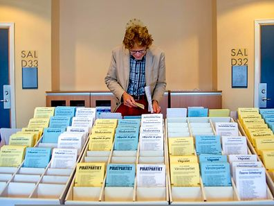 A man chooses among ballot papers at a polling station during the Swedish general election in Goteborg September 14