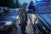 Um membro dos Taliban verifica os documentos das pessoas que viajam de carro.