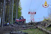 HANDOUT - 23.05.2021, Italien, Stresa: Die Aufnahme der Feuerwehr zeigt Feuerwehrleute an einer abgestürzten Gondel, die in einem Waldstück liegt. Bei dem Seilbahnunglück in der norditalienischen Provinz Verbano-Cusio-Ossola sind neun Menschen ums Leben gekommen, weitere wurden verletzt. Foto: Vigili del Fuoco/dpa - ACHTUNG: Nur zur redaktionellen Verwendung im Zusammenhang mit der aktuellen Berichterstattung und nur mit vollständiger Nennung des vorstehenden Credits +++ dpa-Bildfunk +++