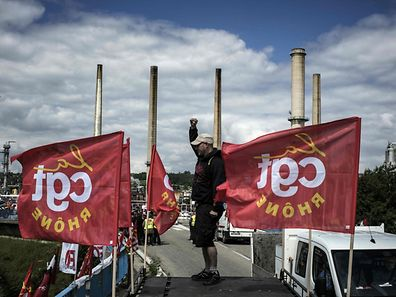 A striking worker stands next to French CGT union flags in front of the Total oil refinery of Feyzin, near Lyon, central-eastern France, on May 24, 2016, during a strike at the plant to protest against government labour reforms. France's government stepped up efforts on May 24 to break blockades and strikes at refineries that are threatening to paralyse the country just three weeks ahead of the Euro 2016 football tournament. Six out of eight of the refineries in France have either stopped operating or have reduced output due to strikes and blockades.  / AFP PHOTO / JEFF PACHOUD