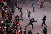 TOPSHOT - Protesters clash with Spanish policemen outside El Prat airport in Barcelona on October 14, 2019 as thousands of angry protesters took to the streets after Spain's Supreme Court sentenced nine Catalan separatist leaders to between nine and 13 years in jail for sedition over the failed 2017 independence bid. - As the news broke, demonstrators turned out en masse, blocking streets in Barcelona and elsewhere as police braced for what activists said would be a mass response of civil disobedience. (Photo by Pau Barrena / AFP)