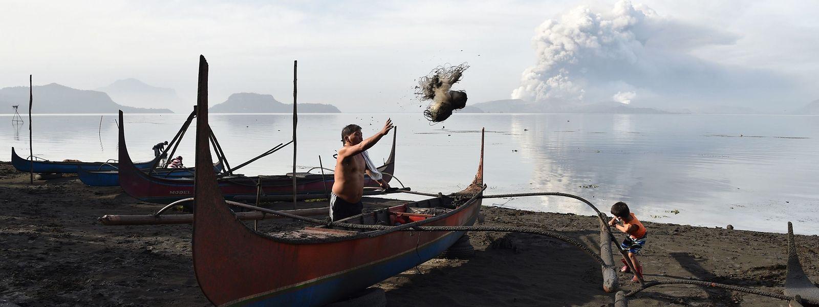 Ein Bewohner der Stadt Tanauan auf den Philippinen entfernt Schlamm und Asche von seinem Auslegerboot, während im Hintergrund eine Rauchwolke über dem Vulkan Taal aufsteigt.